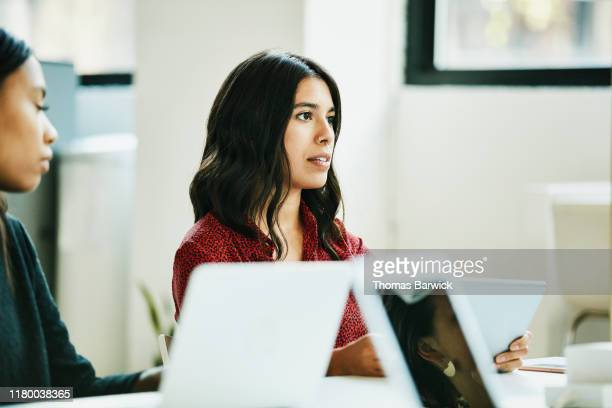Businesswoman leading team meeting in office conference room
