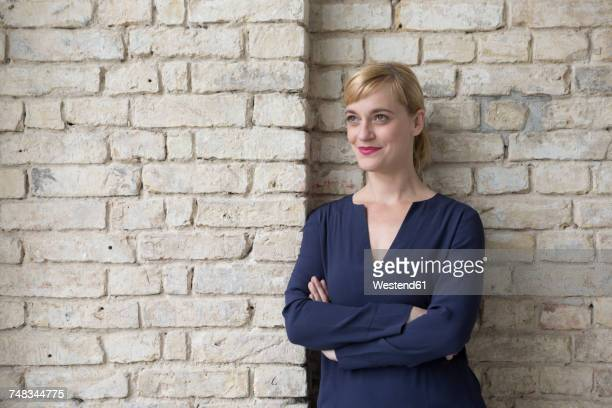 Businesswoman leaning against brick wall, looking away
