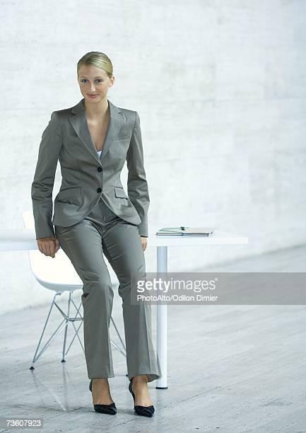 Businesswoman leaning against edge of table, full length portrait