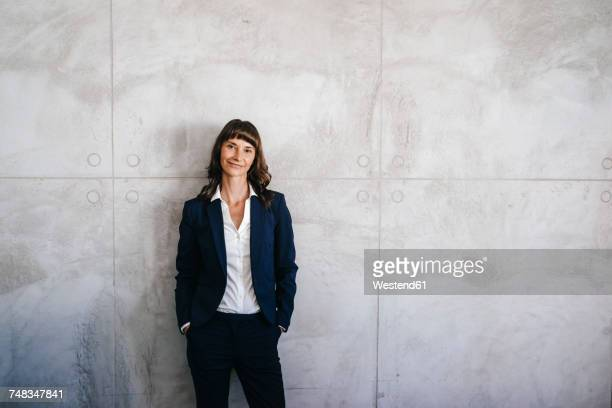 businesswoman leaning against office wall with hands in pockets - anzug stock-fotos und bilder