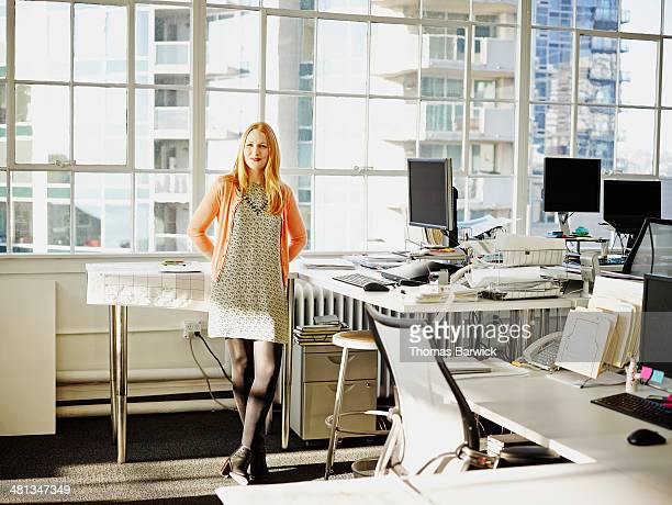 Businesswoman leaning against table in office