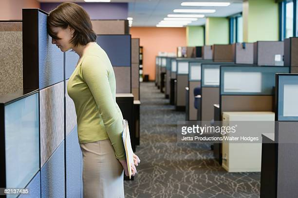 Businesswoman leaning head on cubicle wall