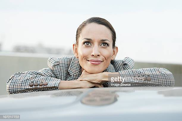 businesswoman leaning on car roof - hand on chin stock pictures, royalty-free photos & images