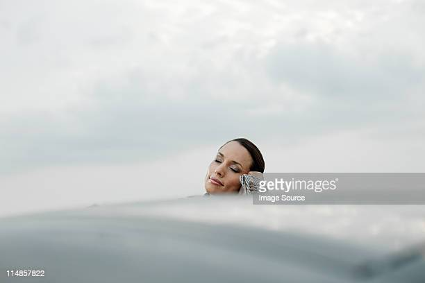 Businesswoman leaning on car roof with eyes closed
