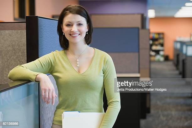 Businesswoman leaning on cubicle wall