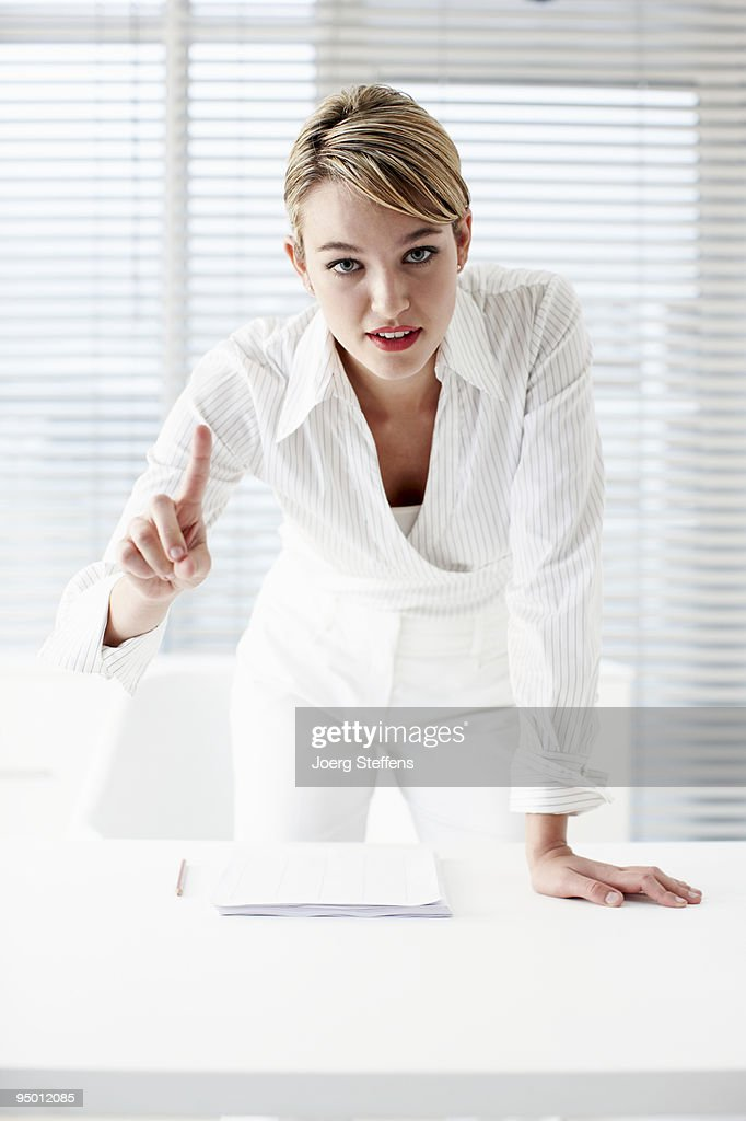 Businesswoman leaning on desk and gesturing with finger : Stock Photo