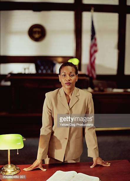 Businesswoman leaning on desk in courtroom, portrait