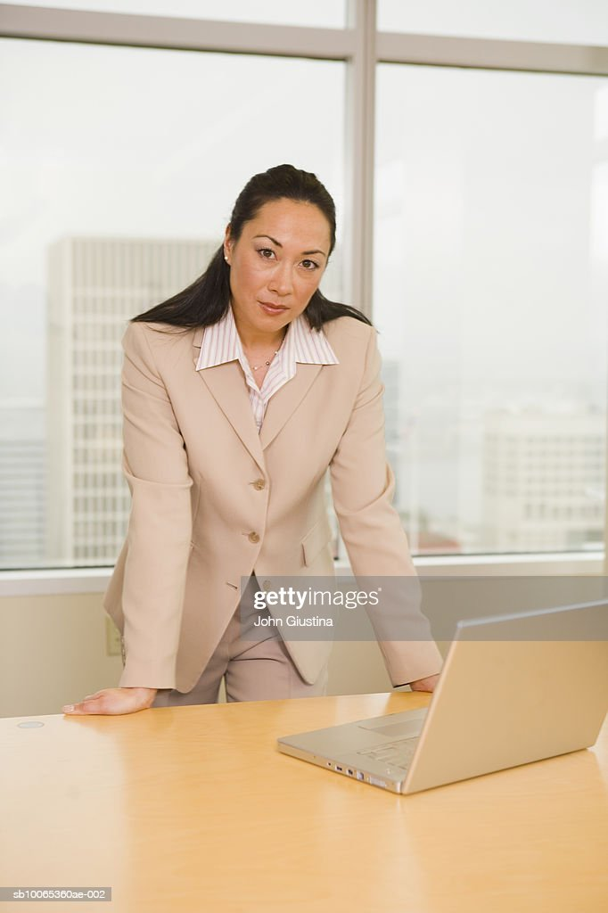 Businesswoman leaning on desk, portrait : Foto stock
