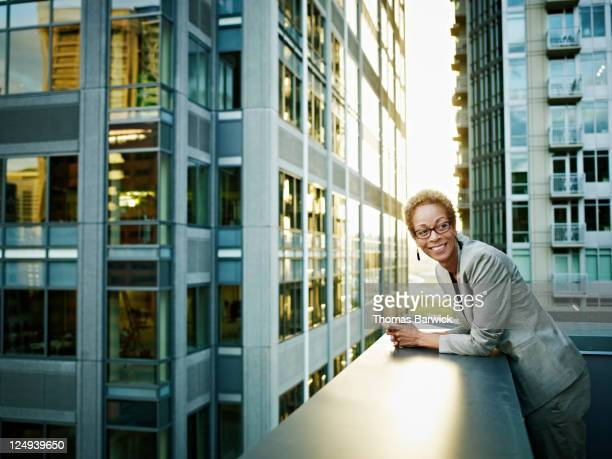 Businesswoman leaning on edge of deck smiling