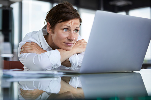 Businesswoman leaning on glass table in office looking at laptop - gettyimageskorea