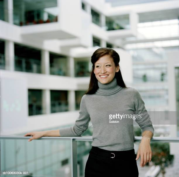 businesswoman leaning on railing, looking away, smiling - タートルネック ストックフォトと画像