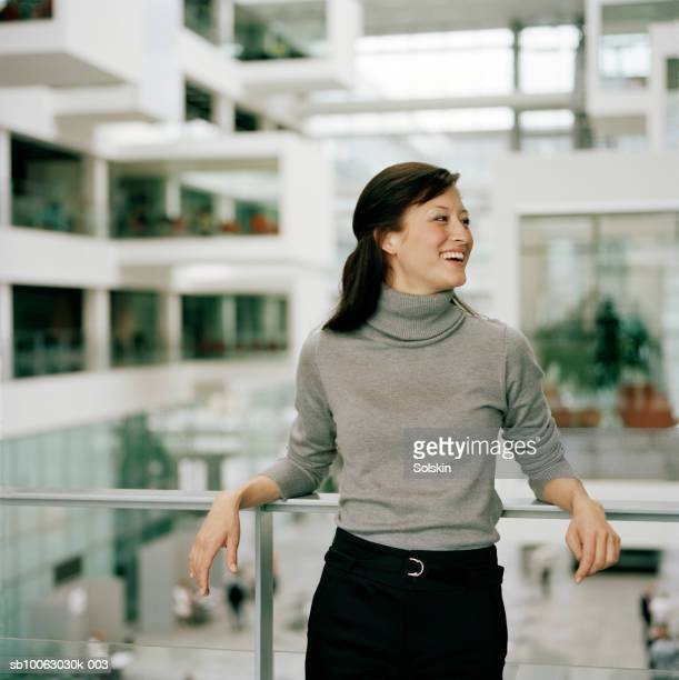 businesswoman leaning on railing, smiling, looking away - タートルネック ストックフォトと画像