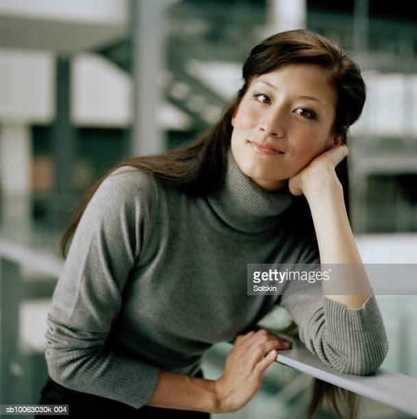 businesswoman leaning on railing, smiling, portrait - タートルネック ストックフォトと画像