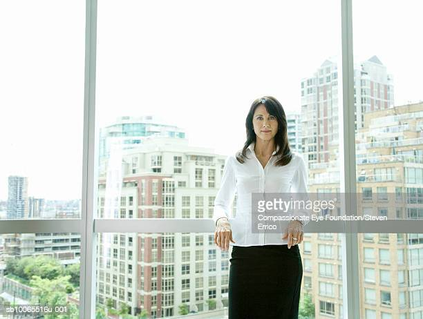 Businesswoman leaning on window with cityscape in background, portrait