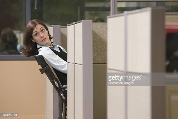 Businesswoman leaning out of her cubicle