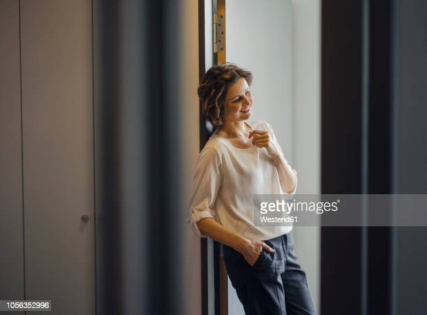 Businesswoman leaning relaxed in door frame of her office