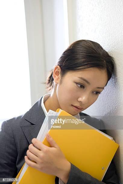 Businesswoman leaningr head on wall