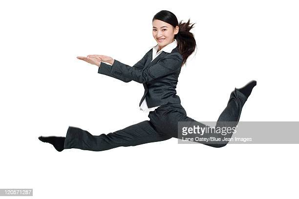 a businesswoman leaping mid-air - 足を開く ストックフォトと画像