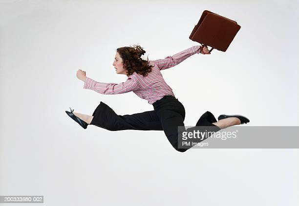 Businesswoman leaping with briefcase, side view