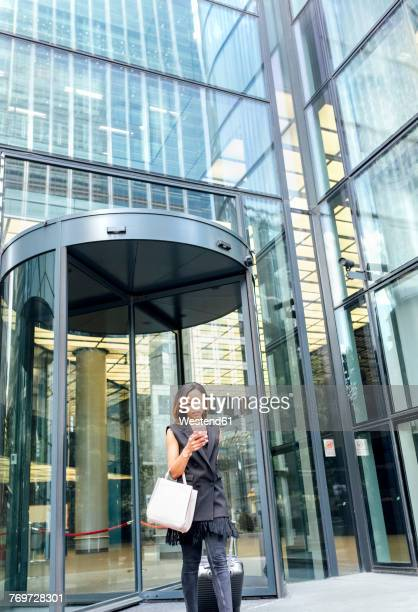 businesswoman leaving an office building in the city - revolve stock pictures, royalty-free photos & images