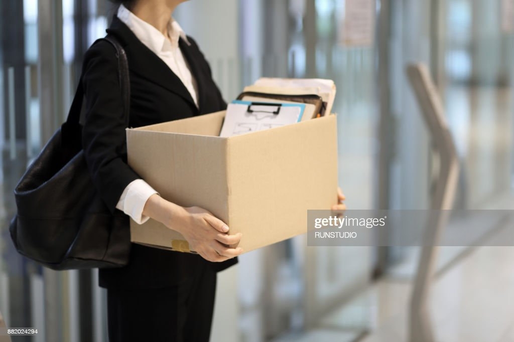 Businesswoman leaving office with box of personal items : Stock Photo