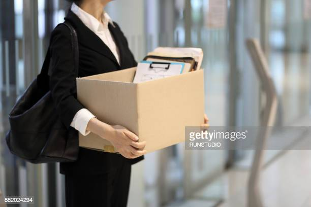 businesswoman leaving office with box of personal items - downsizing unemployment stock pictures, royalty-free photos & images