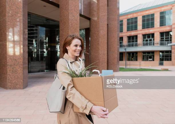 businesswoman leaving the office after quitting her job - quitting a job stock pictures, royalty-free photos & images