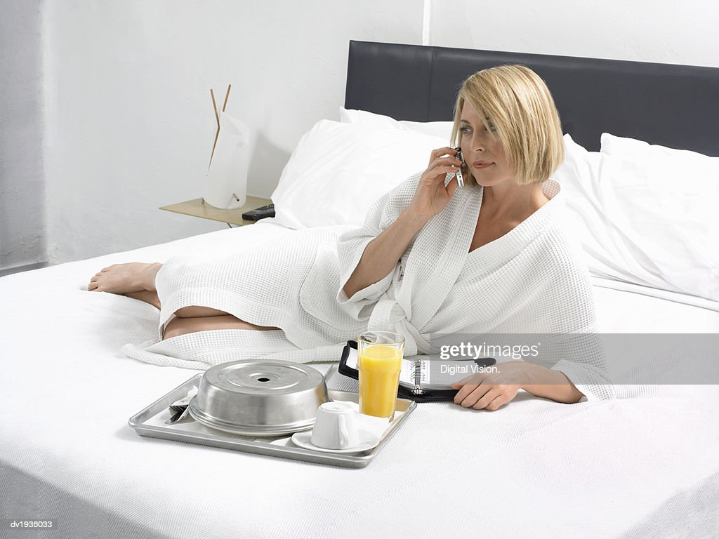 Businesswoman Lies on a Bed in a Hotel Room With a Breakfast Tray and Wearing a Dressing Gown : Stock Photo