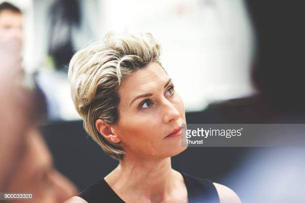 businesswoman listening during meeting - shareholder's meeting stock photos and pictures