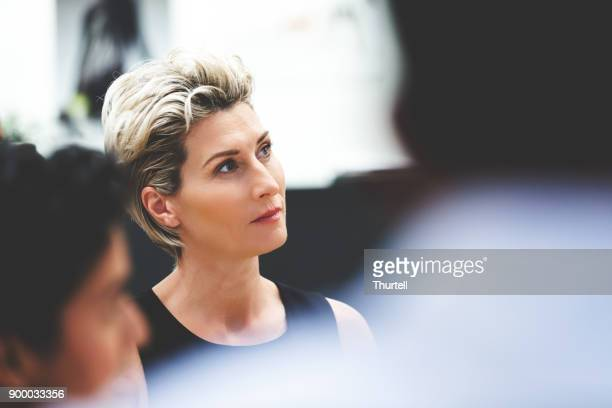businesswoman listening during meeting - differential focus stock pictures, royalty-free photos & images