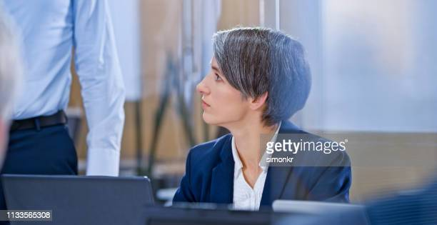 businesswoman listening meeting in glass conference room - blue blazer stock pictures, royalty-free photos & images