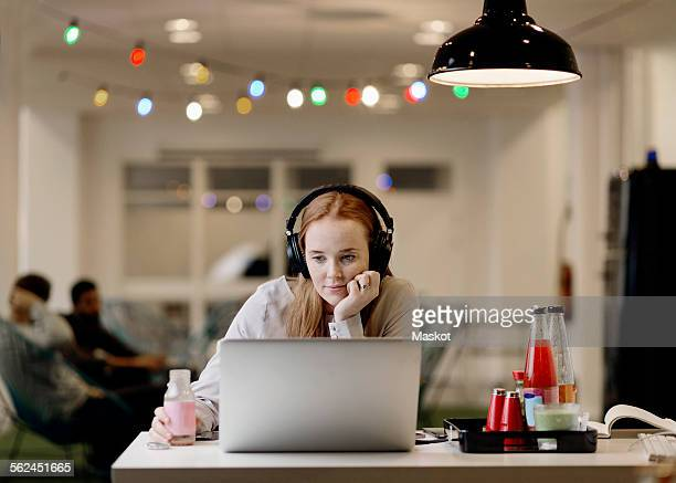 Businesswoman listening music while working late on laptop in creative office