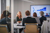 Businesswoman Listening to Associate During Video Conference