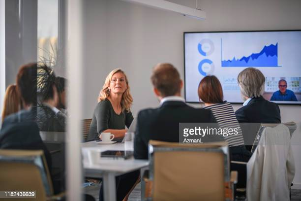 businesswoman listening to associate during video conference - board room stock pictures, royalty-free photos & images