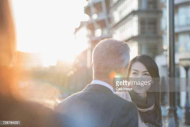 Businesswoman listening to businessman on urban street