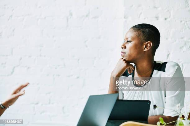businesswoman listening to client during meeting in office conference room - decidere foto e immagini stock