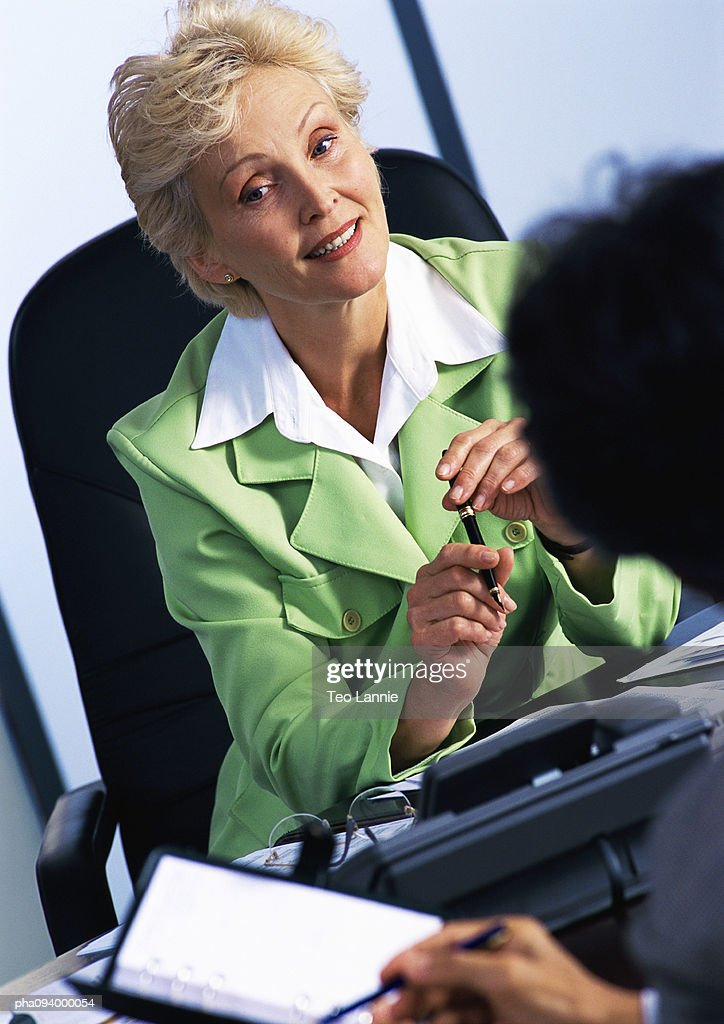 Businesswoman listening to colleague, blurred foreground : Stockfoto