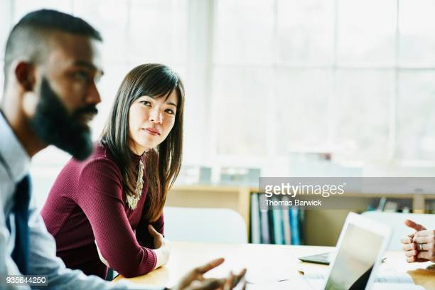businesswoman listening to colleague present during client meeting in office conference room - maroon stock pictures, royalty-free photos & images