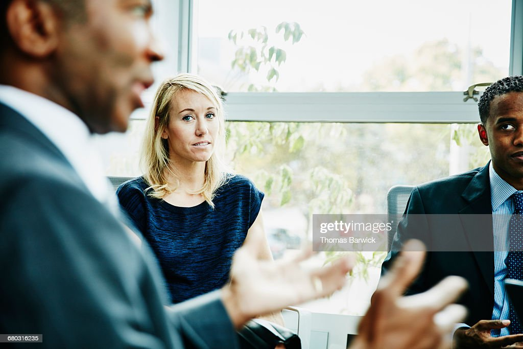 Businesswoman listening to coworker during meeting : Stock Photo