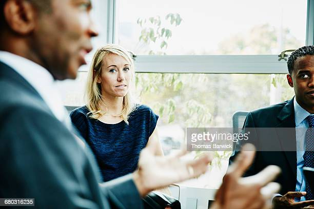 Businesswoman listening to coworker during meeting