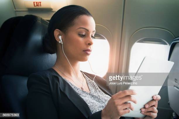 Businesswoman listening to earbuds and digital tablet on airplane