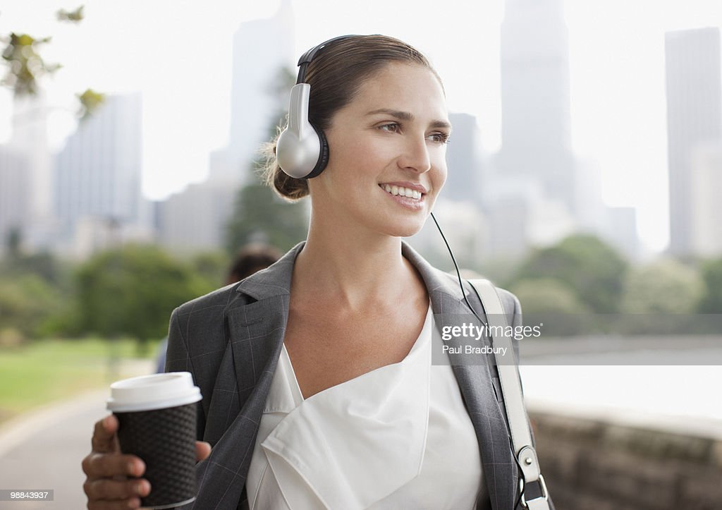 Businesswoman listening to headphones and carrying coffee : Stock Photo