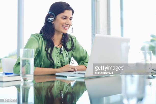 Geschäftsfrau Kopfhörer hören am Schreibtisch