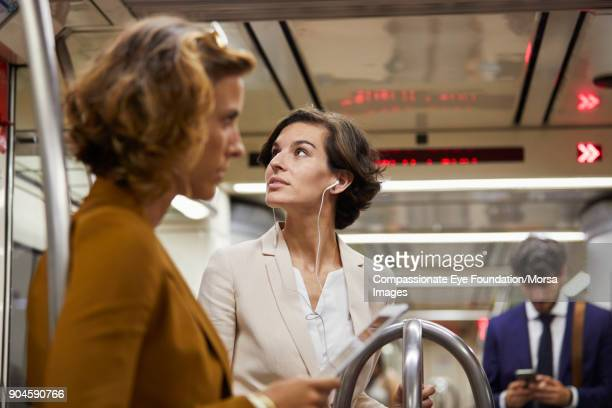 "businesswoman listening to headphones on subway train - ""compassionate eye"" stock pictures, royalty-free photos & images"