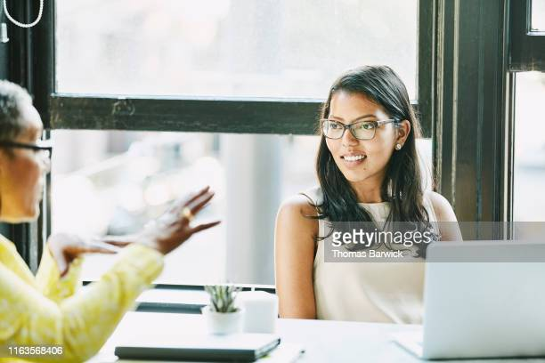 businesswoman listening to ideas from colleague during meeting in office - nosotroscollection stockfoto's en -beelden