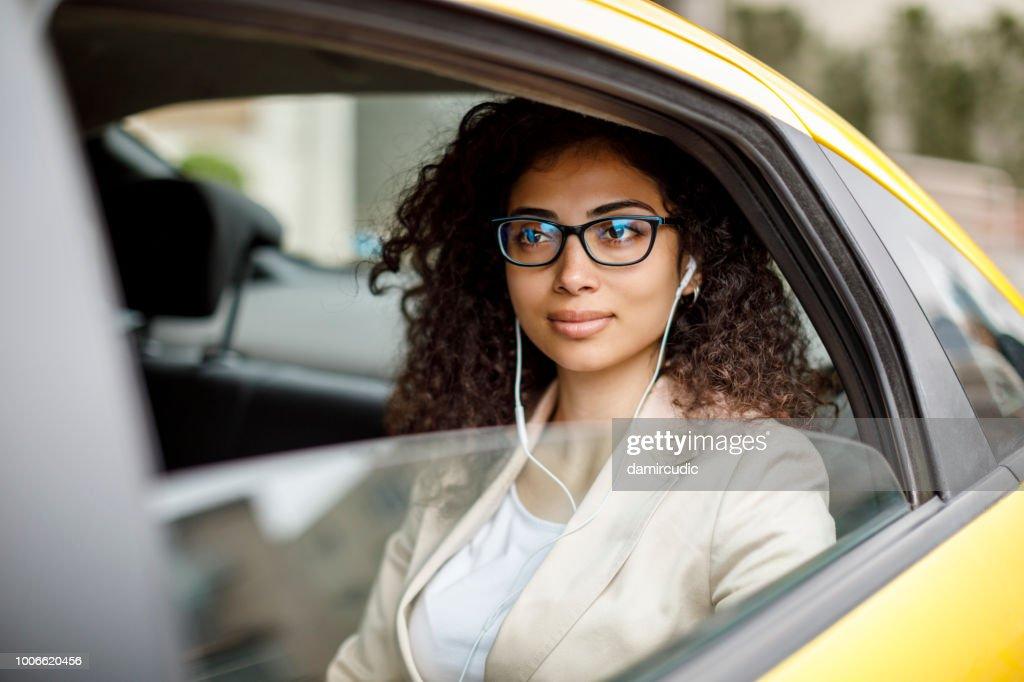 Empresária, ouvir música enquanto pendulares para trabalhar de táxi : Foto de stock