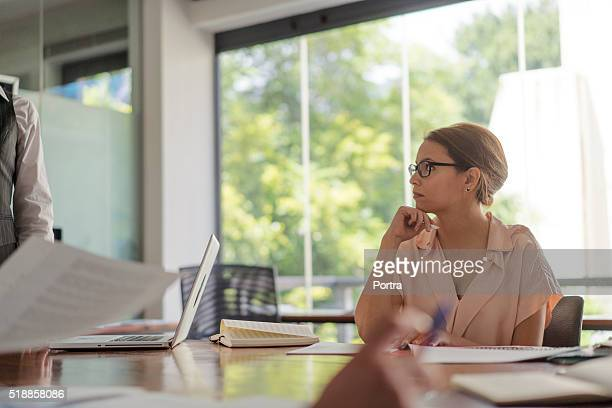 Businesswoman listening to presentation in board room