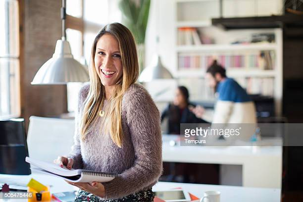 businesswoman looking and smiling at camera in small office. - 30 39 jaar stockfoto's en -beelden