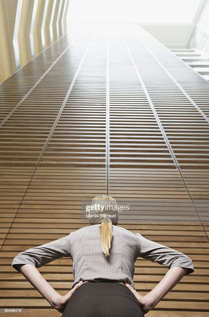 Businesswoman looking at atrium wall : Stock Photo