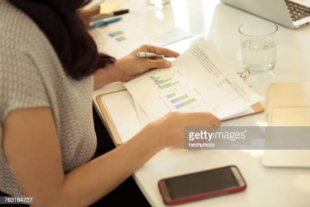 businesswoman looking at bar charts at desk - heshphoto fotografías e imágenes de stock